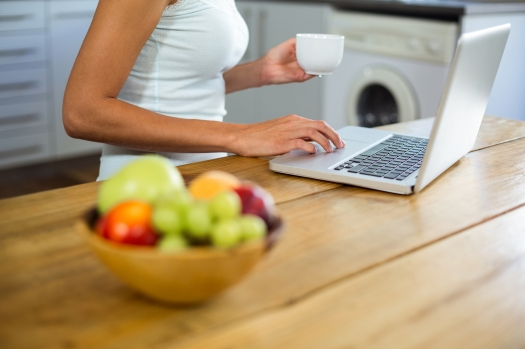 Fruits in bowl on table with woman working on laptop at home
